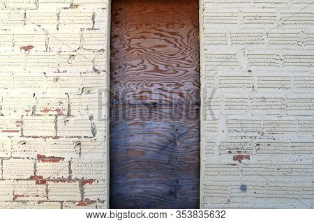 An Old Faded Whitewashed Block Building Wall With A Boarded Up Wood Door