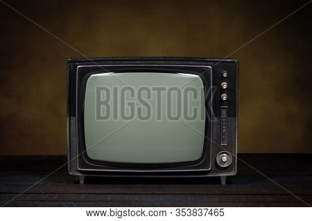 Old Portable Television. Wooden Table And Brown Background. Concept Of Obsolescence, Modernization O
