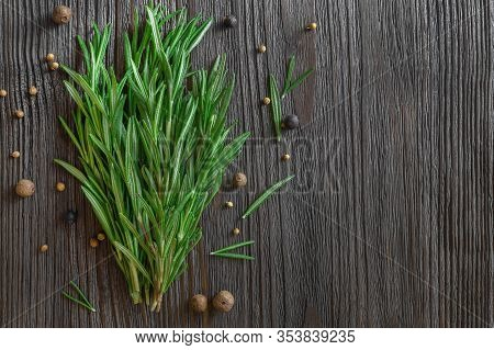Bunch Of Fresh Rosemary And Spices On Dark Wooden Background. Flat Lay, Top View, Copy Space.