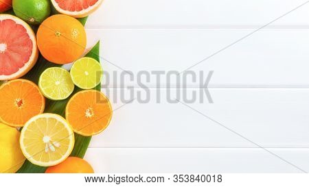 Citrus Fruits With Green Leaves On White Wooden Background. Healthy Food Or Diet Concept. Flat Lay,
