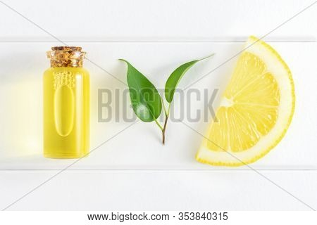 Fresh Lemon Slice, Leaves And Essential Oil On White Background. Flat Lay, Top View, Copy Space.