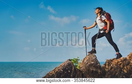Young Asian Women Hikers Climbing Up On The Peak Of Mountain Near Ocean. Woman Hiking In The Mountai