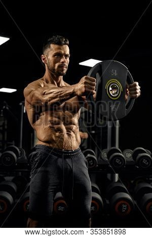 Side View Of Shirtless Tensed Male Bodybuilder Holding Weights Straight Out In Arms. Portrait Of Spo