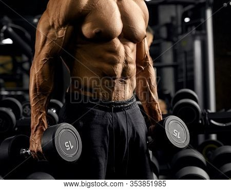 Side View Of Shirtless Incognito Male Bodybuilder Holding Dumbbells In Arms. Close Up Of Sportsman W