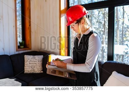 Caucasian Woman Inspector During Pre-purchase Inspection, She Wearing A Red Hardhat And Protective E
