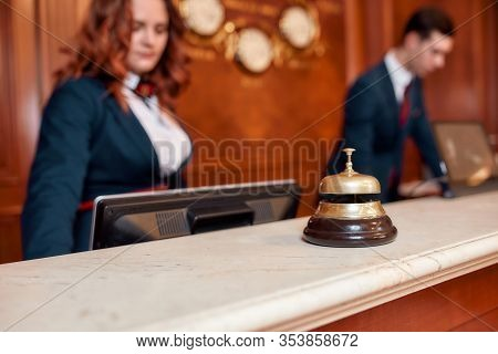 Attractive Executives At The Reception Desk Of A Hotel In The Background. Focus On A Service Bell. H
