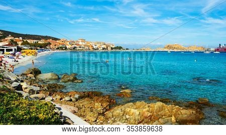 ILE-ROUSSE, FRANCE - SEPTEMBER 22, 2018: People at the main beach of Ile-Rousse, Corsica, France, and the Ile de la Pietra island and a ship at the ferry port on the right