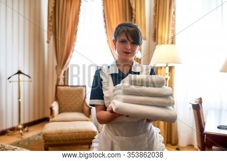 Hotel Maid In Uniform Smiling While Holding Stack Of Clean White Towels For Guests While Cleaning An