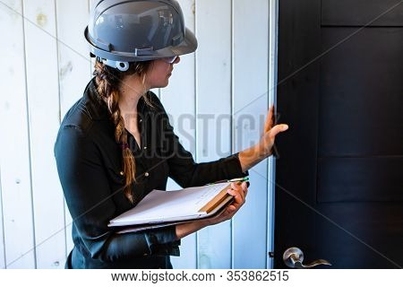 Worker Woman Wears A Grey Hard Hat At Work. Female Construction Inspector Reviews A Room Door During