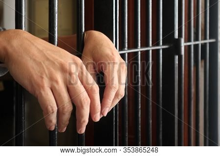 Prisoner Behind Bars.hand Of Prisoner On Steel Jail Bars.man Under Arrested By Policeman Because Ill