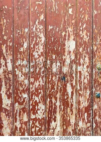 Old Wooden Rustic Door With Peeled Red Paint.