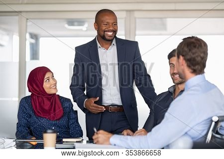 Entrepreneurs, partners and islamic woman conference in meeting room. Happy mature african businessman putting forward his suggestions to colleagues. Group of multiethnic business people brainstorming