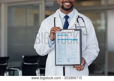 Successful doctor holding hospital admission form. Close up of african doctor holding clipboard with form at hospital. Nurse showing blank medical information document for registration at clinic.