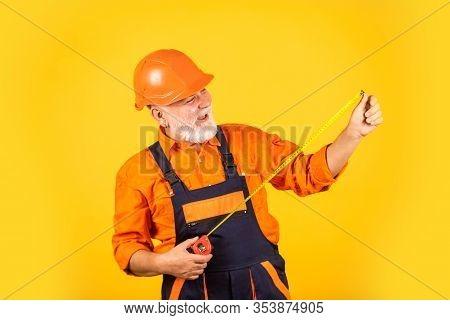 Confident Worker. Engineering And Repair. Happy Carpenter. Handyman Measuring Wall. Senior Builder U