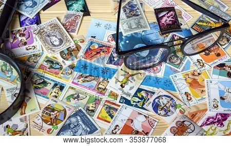 Dolgoprudny, Moscow Region, Russia. 02-24-2020. A Collection Of Postage Stamps. Glasses, A Magnifier