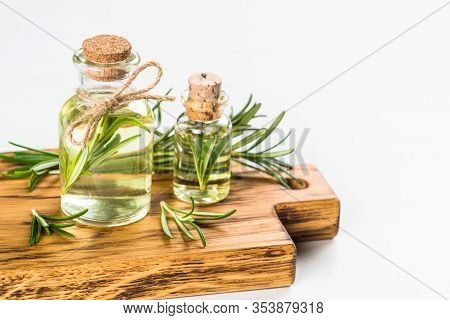 Rosemary Oil. Bottle Glass With Rosemary Essential Oil And Fresh Rosemary Twig On White Background.
