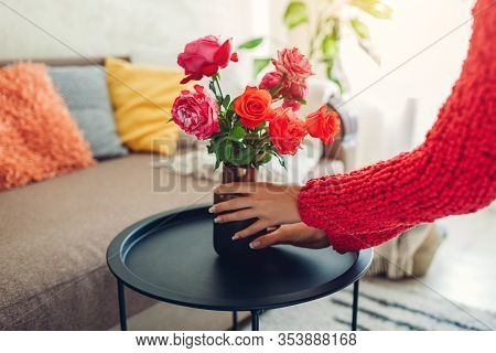 Woman Puts Vase With Flowers Roses On Coffee Table. Housewife Taking Care Of Coziness In Apartment.
