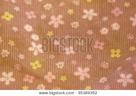 pink and yellow flowers on a brown fabric
