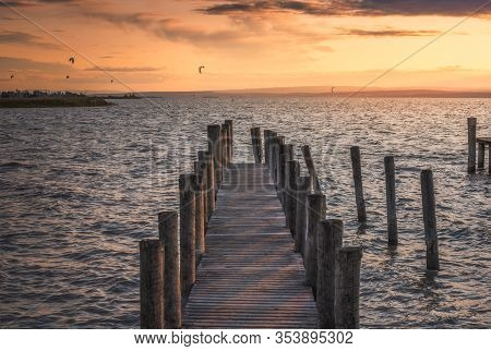 Wooden Pier With Columns On The Lake At Sunset
