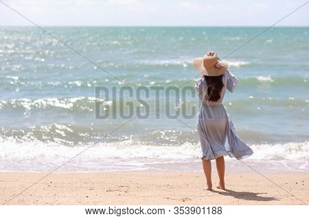 Rear View Happiness Traveller Young Asian Woman In Blue Dress And Hat Standing On Sandy Beach. Cute