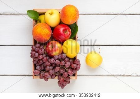 Box Of Fruits With Apples, Peaches And Grape. Top View.