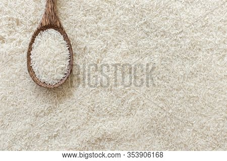 Top View Of Wooden Ladle On Many Rice Texture Background And Copy Space