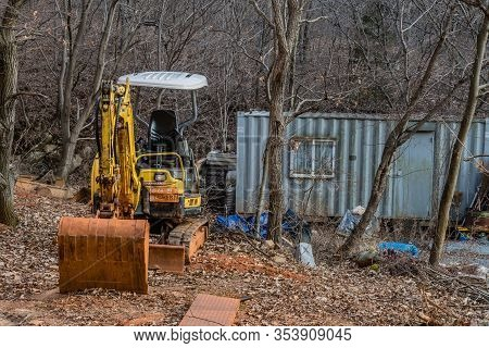 Daejeon, South Korea; March 2, 2020: Yellow Backhoe Sitting Under Leafless Trees Next To Gray Metal