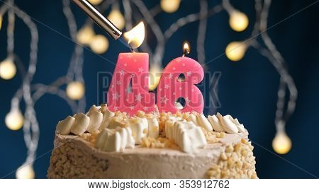 Birthday Cake With 46 Number Pink Candle On Blue Backgraund Set On Fire By Lighter. Close-up View