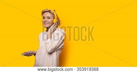 Cheerful Caucasian Blonde Girl Listening To Music From A Phone While Posing Near Yellow Freespace