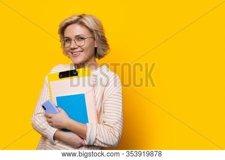 Stunning Blonde Teacher Looking Through Eyeglasses While Holding Some Books And Posing On A Yellow W