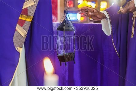 Christian african priest in the altar burning incense