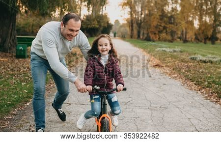Balding Caucasian Father Is Teaching His Daughter To Ride The Bike While Walking Together