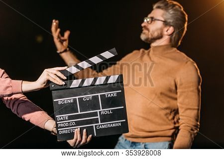 Selective Focus Of Mature Actor Performing Role With Clapboard In Front