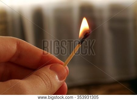 A Burning Match In The Hand Of A Teenager. A Match With A Flame Of Fire On A Dark Background. The Co