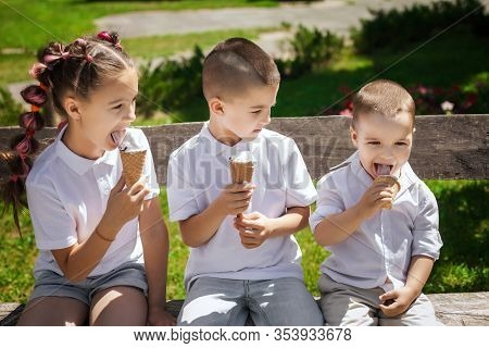 Three Adorable Cute Kids Eating Ice Cream Sitting On A Wooden Bench In The Park. Fun Holiday Concept