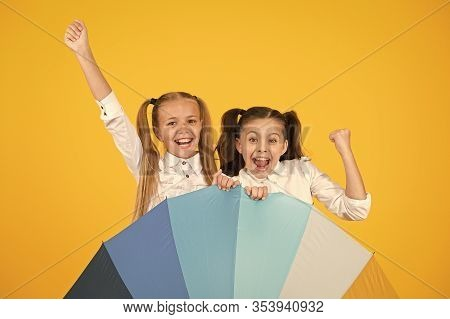 The Coolest Accessory In School. Happy Little Girls Celebrating Autumn Holidays Behind Fashion Acces