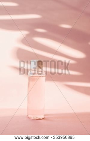 Plastic Bottle With Pink Rose Water On A Pastel Background With Tropical Shadow Of A Palm Leaf. Tran