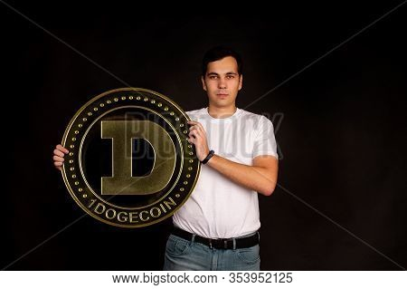 A Young Guy Holds A Symbol Of The Dogecoin Coin, A Modern Currency For Exchange And Purchases. Photo