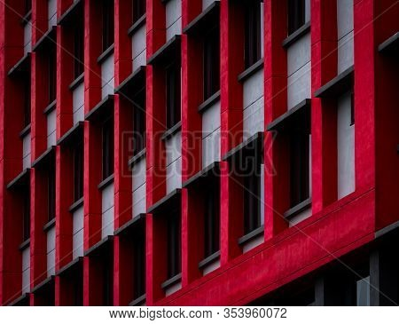 Glass Window Of Skyscraper Office Building With Red And White Concrete Wall. Exterior Commercial Bui