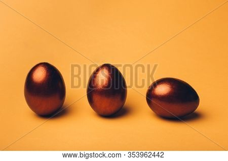 Bronze Easter Eggs On A Yellow Background, Decoration, Holiday Background Concept. Traditions, Relig