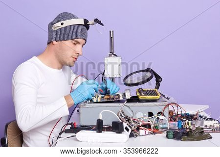 Indoor Shot Of Repairman Using Magnifier And Multimeter While Fixing Pc Motherboard, Profile Of Radi