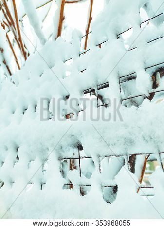 Iron Net Fence Covered Snow. Metal Rusty Fence-mesh Netting In The Snow. Close-up Shot Of Snow On A