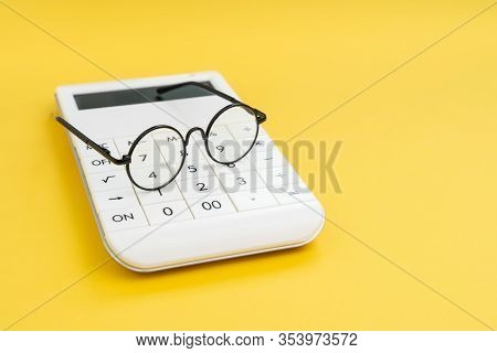 Eyeglasses On White Calculator On Yellow Background With Copy Space Using As Analyze Numbers Or Data