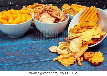 Differnt Types Of Junk Food, Salty-sticks, Salty-crackers On Wooden Table In Still-life