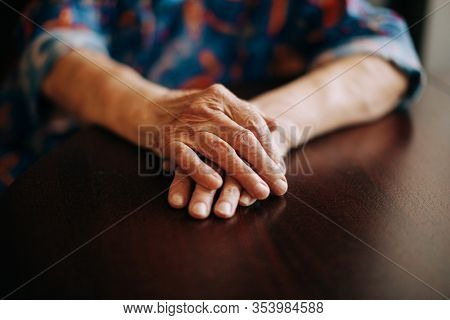hands of real senior woman at home , natural light , selective focus point