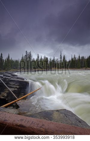 Athabasca Falls In The Rocky Mountains Of Canada. Between The Cliffs Above The Water Stuck Logs. Clo