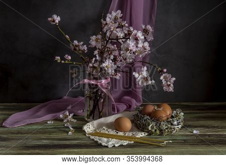 The Easter Composition. The Nest With Eggs, A Almond Branches And Church Candles On Wooden Table Clo