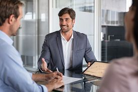 Confident financial agent showing growth graph to couple. Mid couple meeting financial advisor for investment. Business people discussing the charts and graphs showing the results.