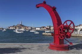 Old Red Painted Crane, In Background Old Town Rovinj - Rovigno, Istria, Croatia