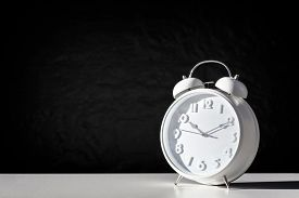 Alarm clock against a black background with copy space